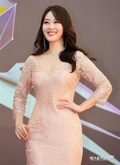 Phát thanh viên Shin Ah Young khoe dáng nuột nà trong chiếc đầm ren hồng pastel cổ thuyền. Mái tóc gợn sóng cùng lối trang điểm nhẹ nhàng giúp tăng thêm độ cuốn hút cho người đẹp.