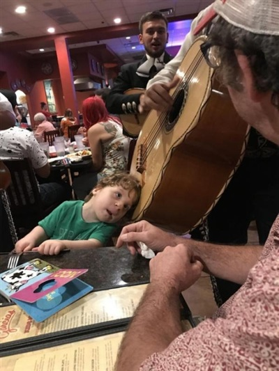 Cậu bé này gần như không nghe được nên người nhạc công đã để cậu áp tai vào cây ghi-ta để cảm nhận được độ rung khi đàn.