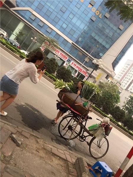 Trong khi hai cô gái thoải mái tạo dáng bên gánh xe hoa loa kèn thì người đàn ông bán hoa chỉ lặng lẽ ngồi một góc nhìn từ xa