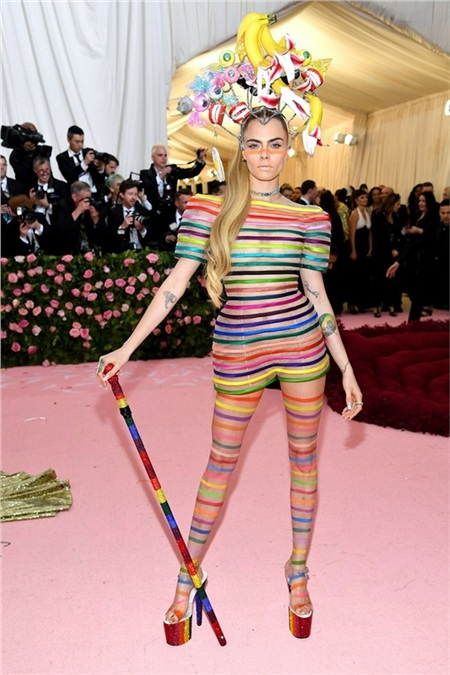 Cara Delevingne đội nguyên nải chuối và kẹo ngọt lên đầu, trong khi 'che thân' bằng bộ trang phục xuyên thấu. Nữ người mẫu ủng hộ cộng đồng LGBTQ với những đường vân lục sắc.