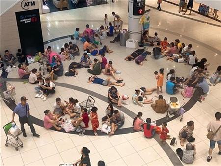 Người dân ngồi bệt, nằm vạ vật dưới sàn nhà Aeon Mall