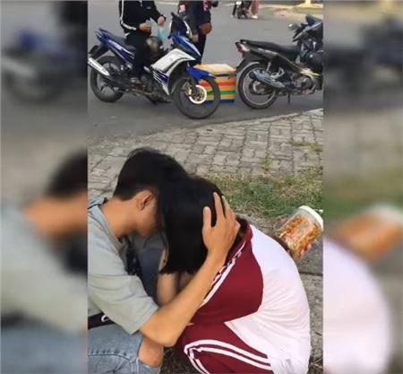 Chàng trai vỗ về bạn gái khi cô nàng xúc động ngồi khóc bên đường.