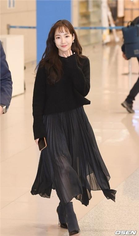 Là người đẹp nổi tiếng tại xứ sở kim chi nhưng Park Min Young ít khi nào ăn mặc rườm rà, đặc biệt là trong những lúc đời thường như thế này. Cách cô nàng mix giữa áo len và chân váy dài tuy đơn giản nhưng hiệu quả. Tuy nhiên, thay vì chọn cả set đen như Park Min Young, các bạn gái có thể thay thành những tông màu khác tươi sáng và đúng tinh thần ngày Tết hơn. Hãy nhớ kết hợp áo và váy có sắc độ màu khác nhau để tránh sự sặc sỡ quá mức (với những tông màu tươi và chói như hồng, đỏ…) hoặc nhàm chán (với các màu trung tính) nhé!