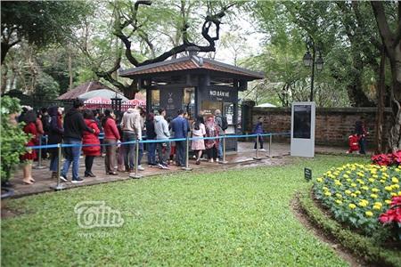 Chiều mùng 1 Tết, khi trời đã dứt cơn mưa, nhiều người dân Hà Nội xếp hàng mua vé vào Văn Miếu.