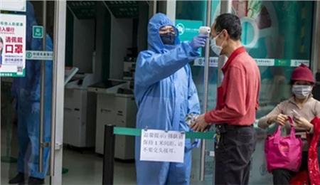 Nhân viên an ninh kiểm tra thân nhiệt khách hàng tại cửa vào một ngân hàng ở tỉnh Quảng Châu - Trung Quốc hôm 24-2. Ảnh: EPA