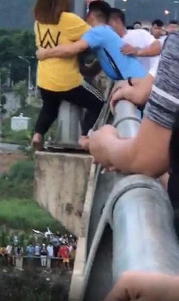 Minh (áo xanh) từ từ tiếp cận và ôm chặt cô gái lôi vào trong an toàn.