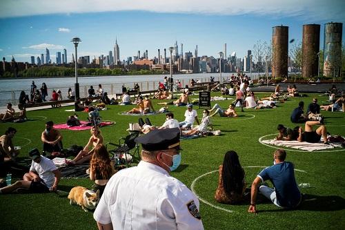 Người dân New York ngồi tắm nắng trong những vòng tròn giãn cách tại công viênDomino. Ảnh: Reuters