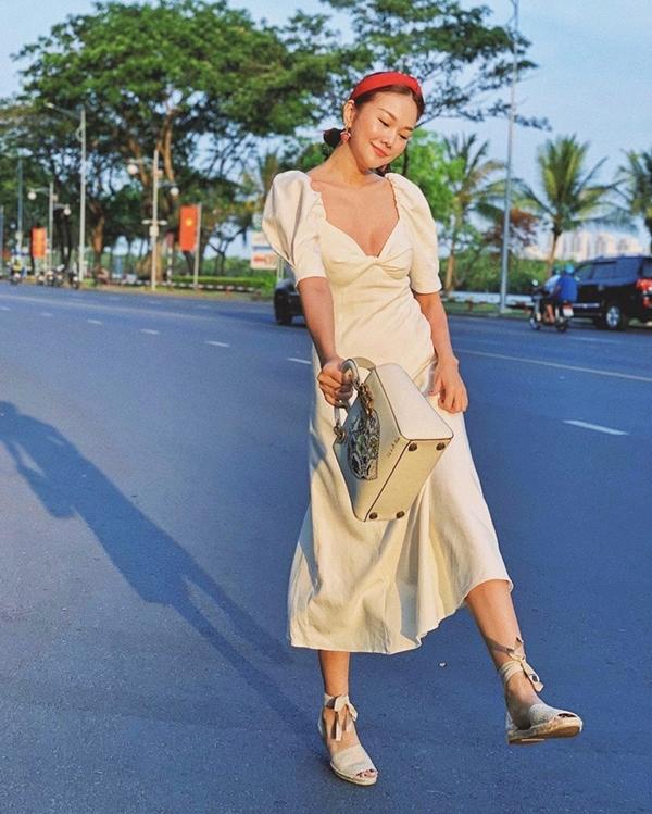 Váy trắng là một trong những xu hướng thời trang 'hot xình xịch' mùa hè 2020, và Thanh Hằng đã kịp bắt trend này khá nhanh nhạy. Chọn cho mình một thiết kếtay bồng cổ điển, nàng siêu mẫu còn phối đầm với sandals buộc dây điệu đà, điểm xuyết khăn turban màu sắc rạng rỡ và đặc biệt là chiếc túi Lady Dior đắt giá.
