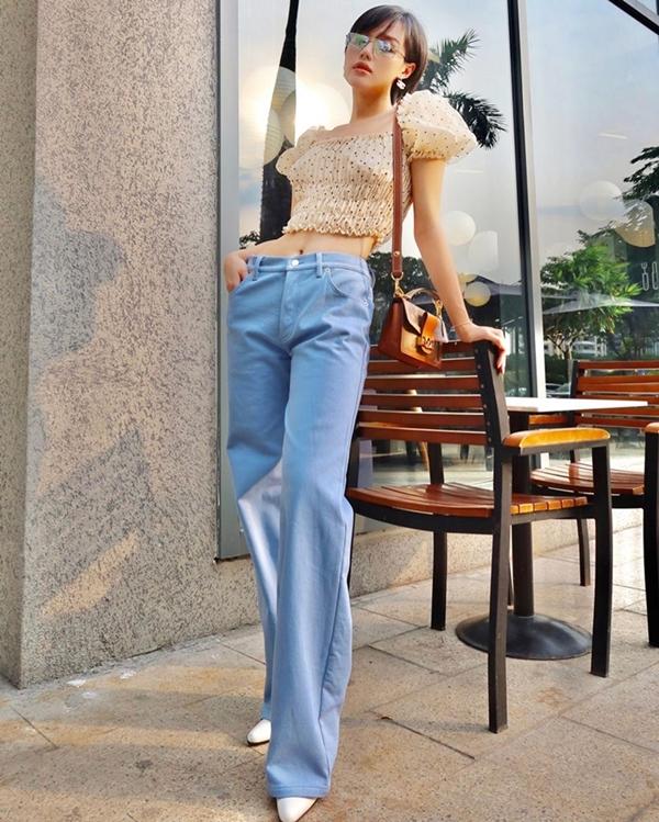Khánh Linh phô diễn vòng eo thon cùng đôi chân dài miên man với bộ đôi crop top chấm bi và quần jeans xanh cổ điển. Để nâng tầm cho set đồ, cô nàng sử dụng phụ kiện kính mắt và túi Louis Vuitton nhỏ nhắn.