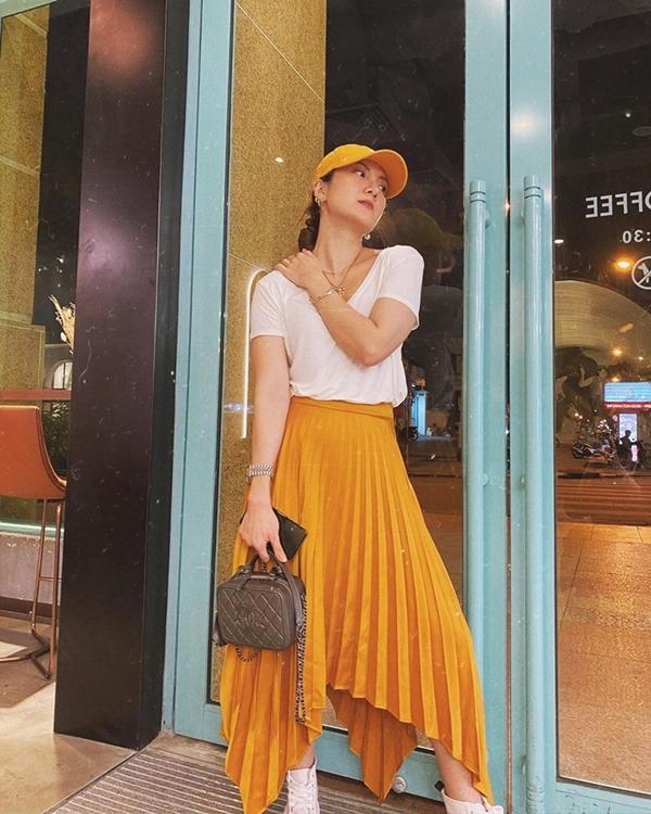 Yến Nhi trổ tài mix đồ sành sỏi khi kết hợp áo phông trắng và chân váy xếp ly cam, rồi điểm xuyết mũ lưỡi trang cùng boots cao gót đồng điệu với tổng thể.