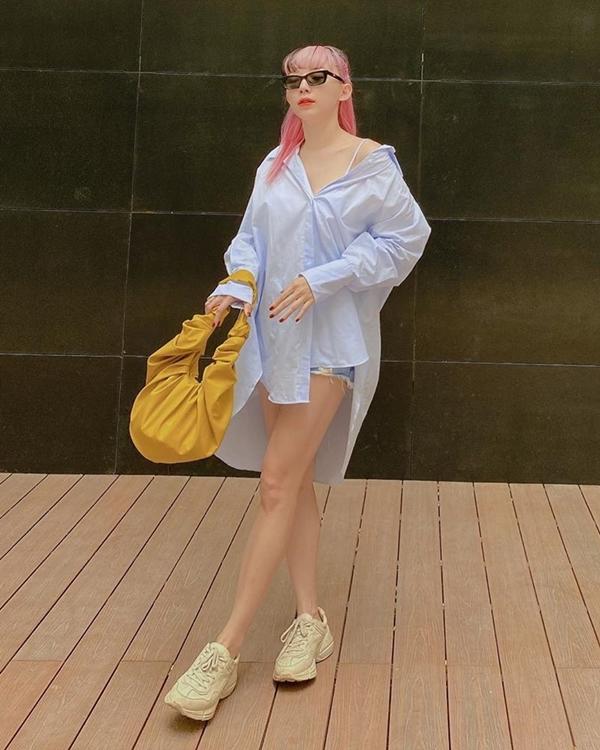 Tóc Tiên chọn mốt giấu quần sexy với chiếc sơ mi phom rộng, mặc cùng shorts jeans. Để tạo điểm sáng cho bộ cánh mát mẻ, cô sử dụng chiếc túi tông vàng nổi bật cùng sneakers khỏe khoắn.