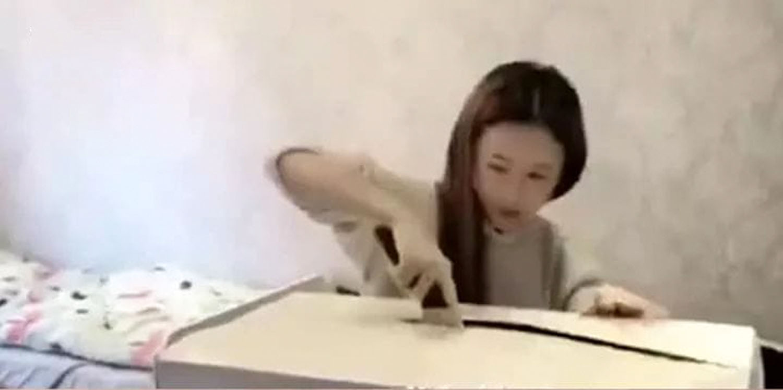 Ngay sau đó, cô đãdùng một con dao khá sắc nhiệt tình rạch một đường sâu ngay chính giữa hộp.