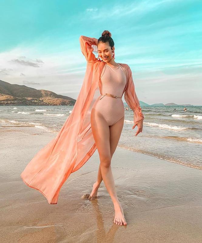 Thiết kế áo choàng dài không chỉ giúp Lan Khuê thêm phần nổi bật trên bãi biển mà còn có tác dụng chống nắng một ít…
