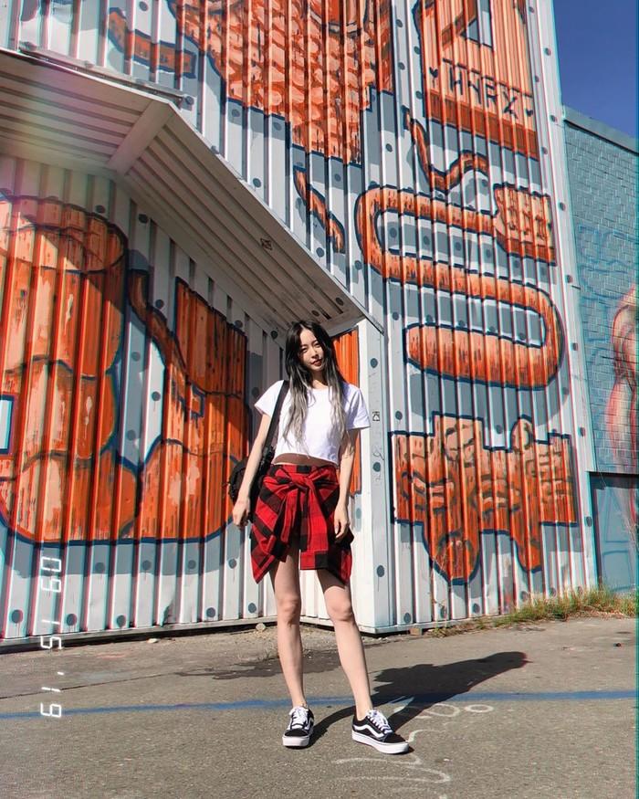 Diện áo croptop trắng và áo sơ mi ca rô đỏ quấn quanh hông phối cùng giày thể thao năng động khoe đôi chân dài thon gọn Han Ye Seul trông giống như một cô nàng sinh viên Đại học