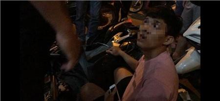 Nam thanh niên bị người dân vây bắt vì nghi giật điện thoại của tài xế xe ôm công nghệ.