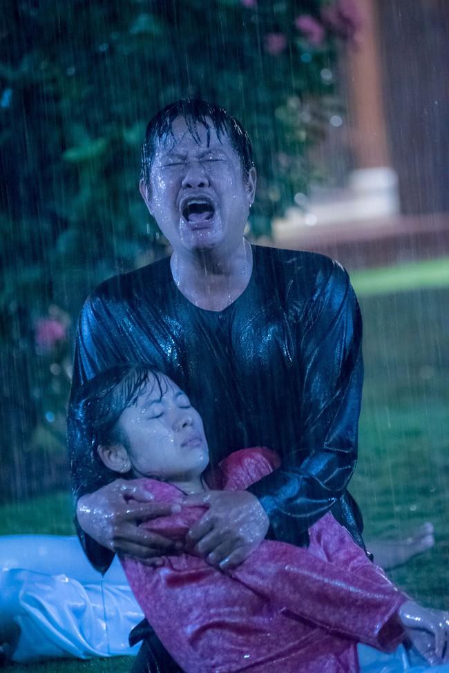 Ông Quý ôm con gái gào khóc giữa trời mưa bão.