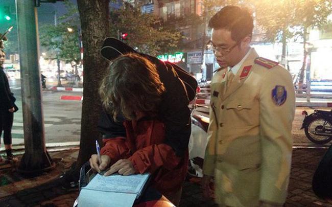 Bị CSGT dừng xe vì không đội mũ bảo hiểm, thanh niên người nước ngoài mang đàn ra ngồi hát 1