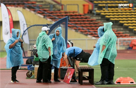 Các nhân viên trong sân mặc áo mưa kiểm tra lại đồ đạc chuẩn bị cho trận đấu còn lại.