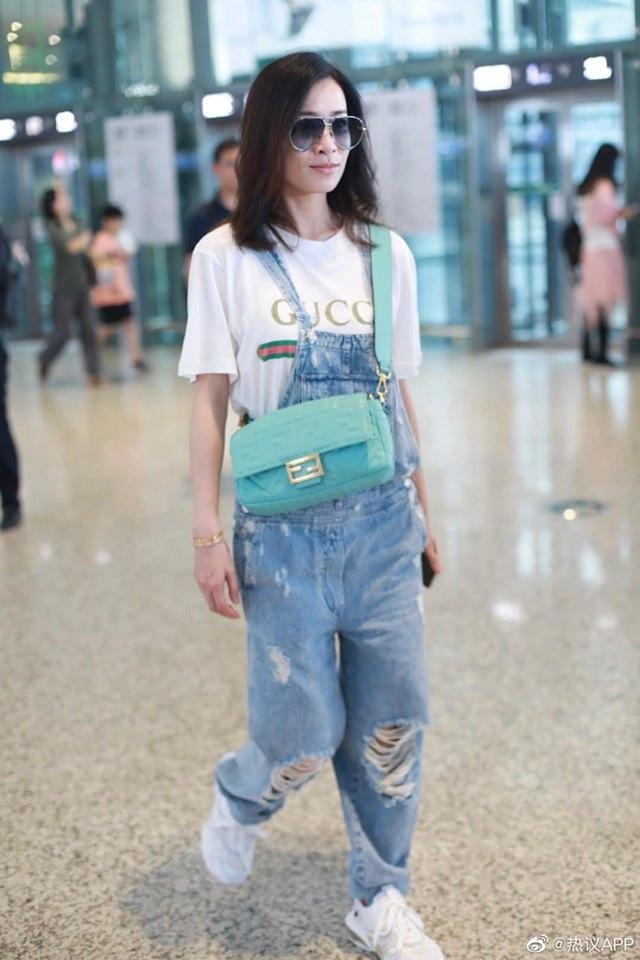 Thiết kế Yếm jeans rách cùng áo phông Gucci oversized được Xa Thi Mạn mix đầy cá tính , không quên tô đậm set đồ với mắt kiếng to màu xanh sẫm